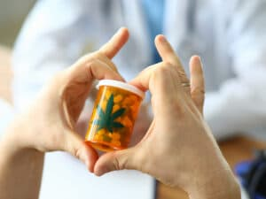 person holding medical marijuana pills with hands in heart shape